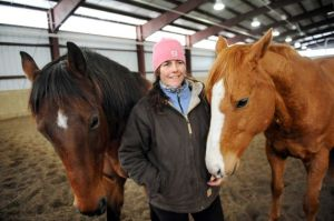 Horsewoman Valerie Buck with Whiskey, left, and Budder on Wednesday, Jan. 7, 2015, at Long Shadows Farm in Cambridge, N.Y. Buck, formerly with Saratoga War Horse, has started a new equine therapy program for women who have experienced trauma called ACTT Naturally. (Cindy Schultz / Times Union)